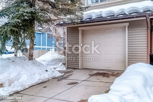 istock White garage door entrance of home with snow covered roof and yard in winter 1298057956