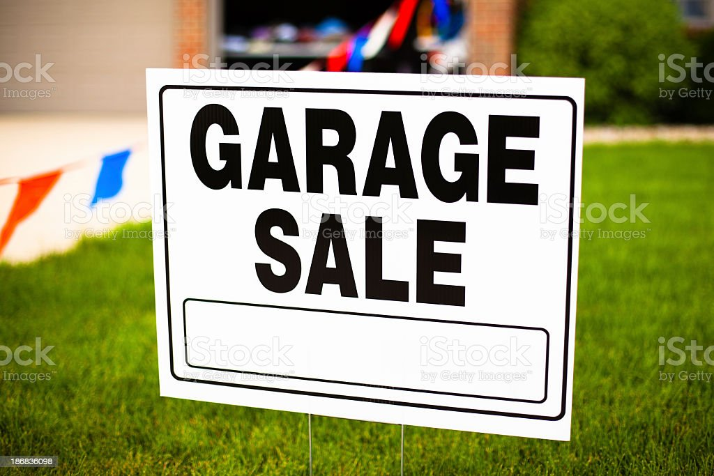 White garage sale sign on grassy lawn  stock photo