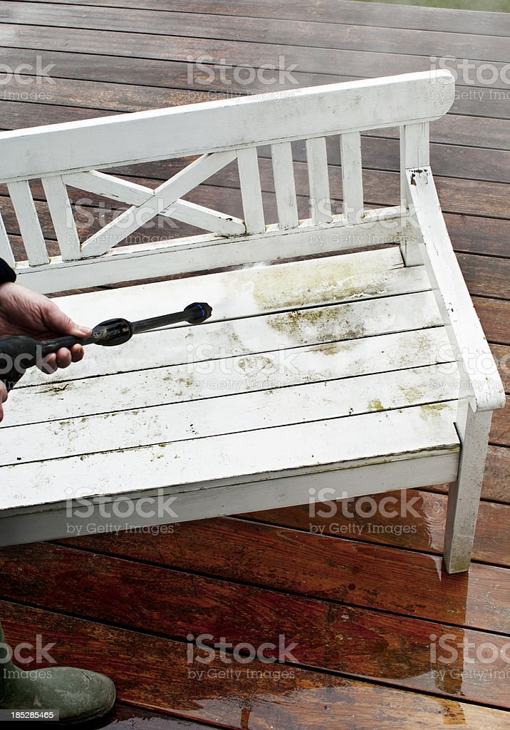 White Garden Bench Being Jet Washed On Wooden Deck Stock