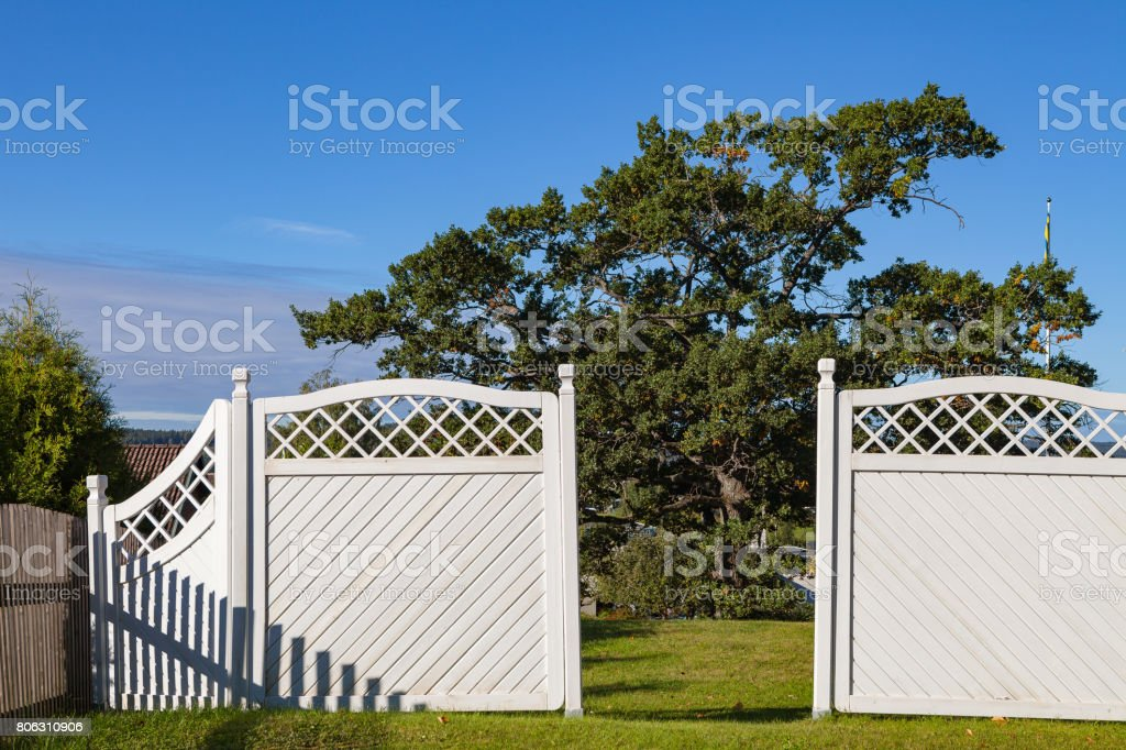 White garden wooden fence and gates to yard with green grass and trees stock photo