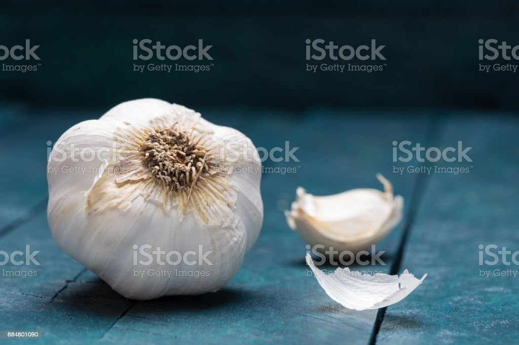 White garlic on petrol-colored wooden background - foto stock