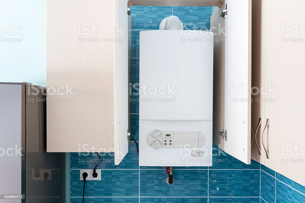 White gas boiler mounted in wall cupboard stock photo
