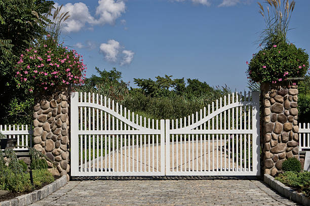 White gate in front of a house A fancy gate in front of a house. gated community stock pictures, royalty-free photos & images