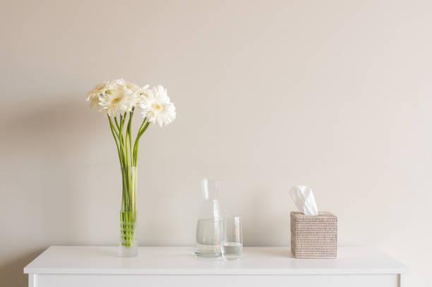 weiße gerbera mit wasser krug und tissue box regal - anrichte weiß stock-fotos und bilder