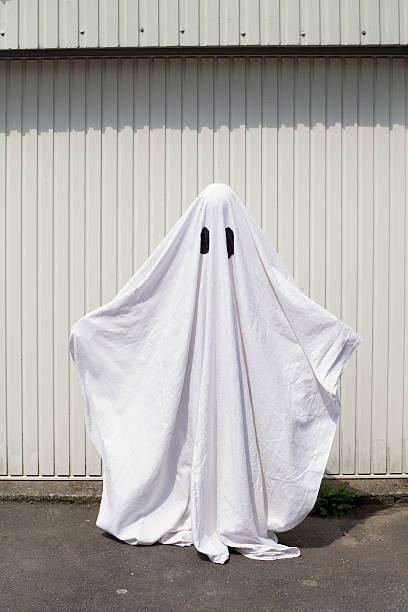 white ghost in front of a garage door - geist kostüm stock-fotos und bilder