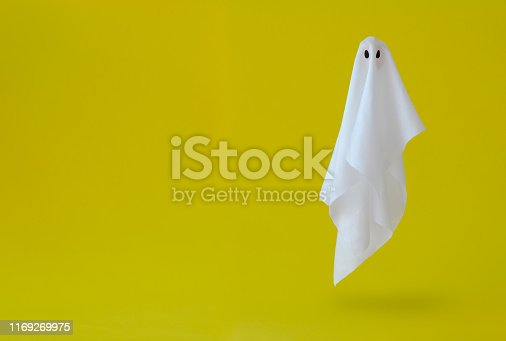 White ghost sheet costume flying in the air with yellow background. Minimal Halloween scary concept.