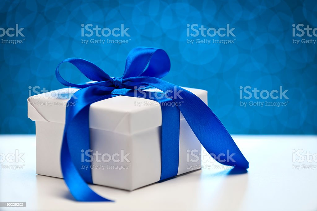 White gift box against blue bokeh lights stock photo