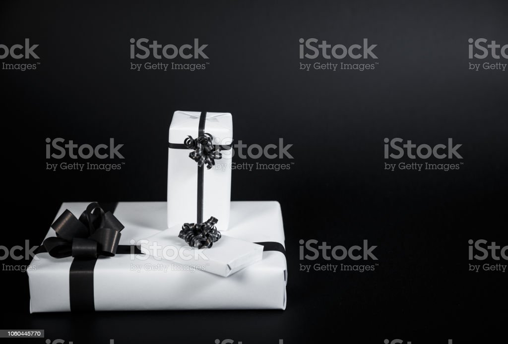 White gift box on a dark contrasted background, decorated with a textured bow, creating a romantic atmosphere. stock photo