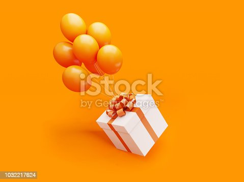 White gift box tied with orange colored ribbon is carried away by orange colored balloons on orange background.  Horizontal composition with copy space, Great use for Christmas and Valentine's Day related gift concepts.