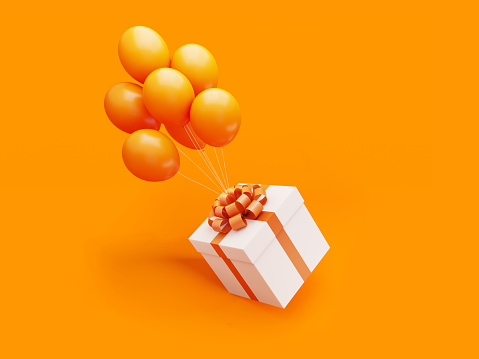 White Gift Box Tied with Orange Ribbon Is Carried Away By Orange Colored Balloons