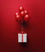White gift box tied with red ribbon is carried away by red balloons on red background. Vertical composition with copy space, Great use for Christmas and Valentine's Day related gift concepts.