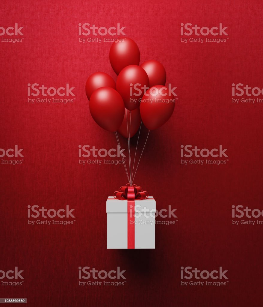 White Gift Box Tied With Red Ribbon Is Carried Away By Red Balloons stock photo