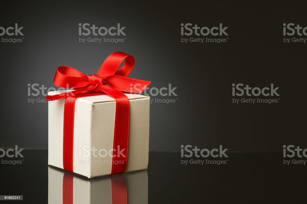 White gift box with a red ribbon tied around it royalty-free stock photo