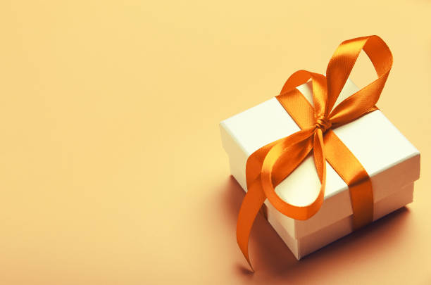 White gift box with orange bright ribbon on yellow background. Beautiful gift for the new year, Christmas, birthday. Copy space White gift box with orange bright ribbon on yellow background. Beautiful gift for the new year, Christmas, birthday. Copy space. gift box stock pictures, royalty-free photos & images