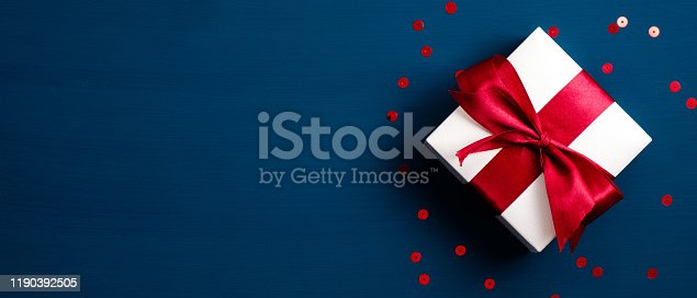 White gift box with red ribbon bow on blue background with confetti. Christmas present, valentine day surprise, birthday concept. Flat lay, top view.
