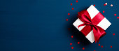 istock White gift box with red ribbon bow on blue background with confetti. Christmas present, valentine day surprise, birthday concept. Flat lay, top view. 1190392505