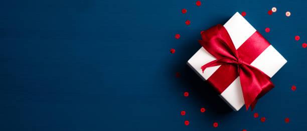 białe pudełko z czerwoną wstążką na niebieskim tle z konfetti. prezent bożonarodzeniowy, walentynkowa niespodzianka, koncepcja urodzinowa. płaski lay, widok z góry. - gift zdjęcia i obrazy z banku zdjęć