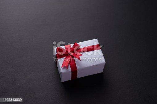 White gift box with red ribbon, light coloured background flat lay for stock image