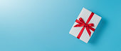 istock white gift box with red ribbon on blue isolated background. 1181163491