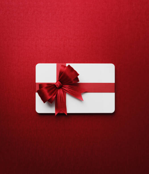 White Gift Card With Red Bow Tie On Red Background White gift card with red bow tie on red background. Vertical composition with copy space. gift card stock pictures, royalty-free photos & images