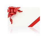 White gift card with a red bow tie isolated on white reflective background. Gift card is left blank for custom copyspace. A red satin bow tie is located on gift card`s upper left corner.Clipping path is included. Great use for christmas, valentines day, sale and gift related concepts.