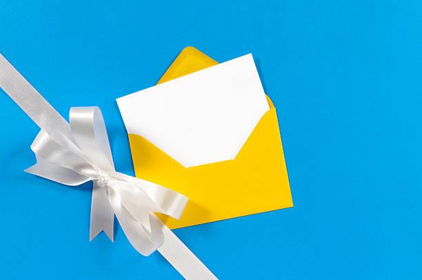 white gift ribbon on blue paper with yellow envelope - blue yellow band bildbanksfoton och bilder
