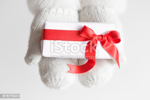 istock White gift with red ribbon in winter gloves. Congratulation concept. 873275424
