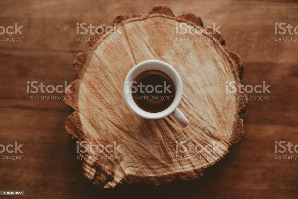 White glass cup of coffee espresso on sawed wood. Top view stock photo