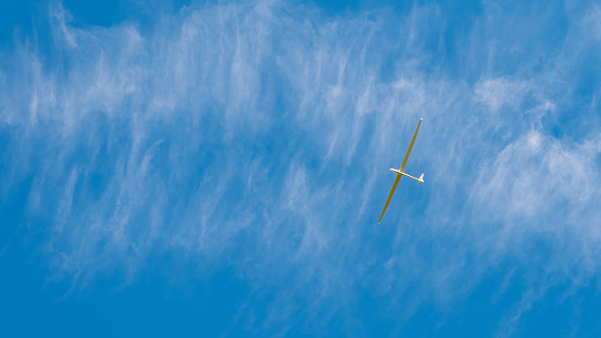 White glider aircraft hovering over the blue sky during delicately cloudy day.