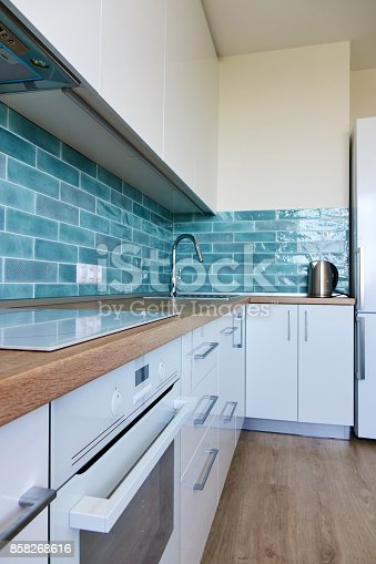 607472174 istock photo White glossy kitchen with modern appliances 858268616