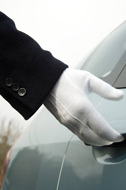 white gloved uniformed hand opening car door - limousine service stock photos and pictures