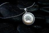 istock White gold pendant with Nacre and diamonds on black stones background 882347060