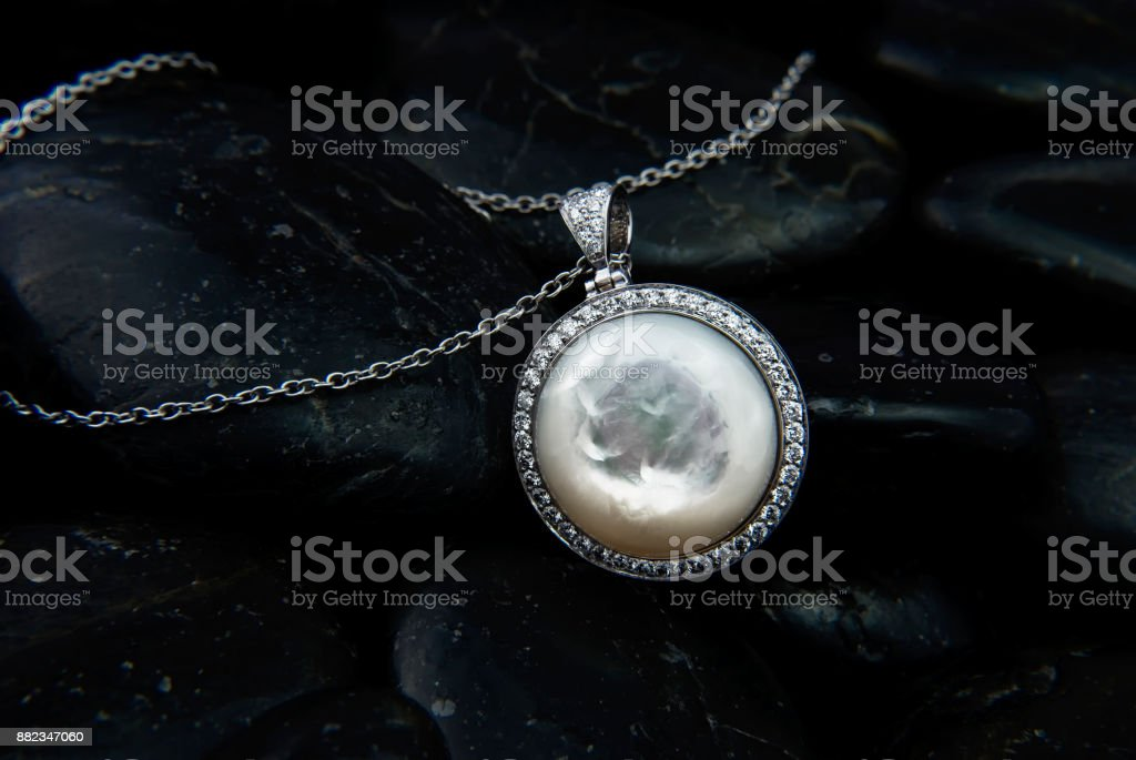 White gold pendant with Nacre and diamonds on black stones background stock photo