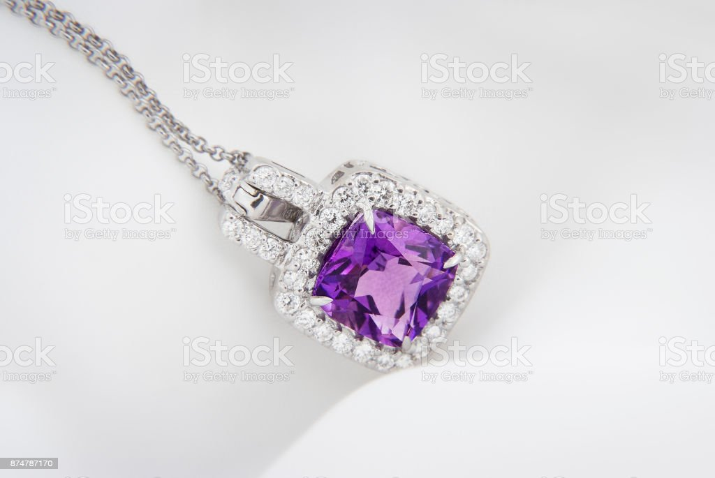 White gold pendant with rose violet amethyst and diamonds on soft  blurred background stock photo