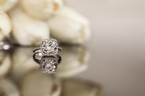 istock White gold wedding ring on flower background 928559684
