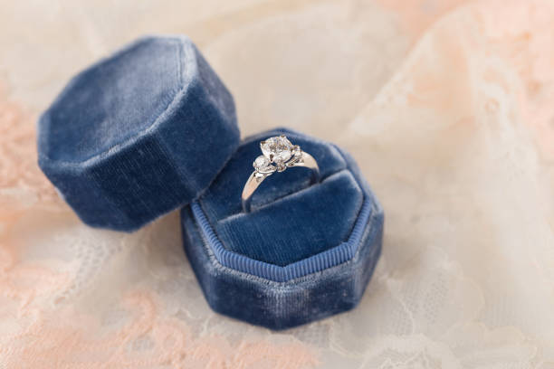 White golden wedding ring with diamonds in blue vintage velvet ring box on pink lace background stock photo
