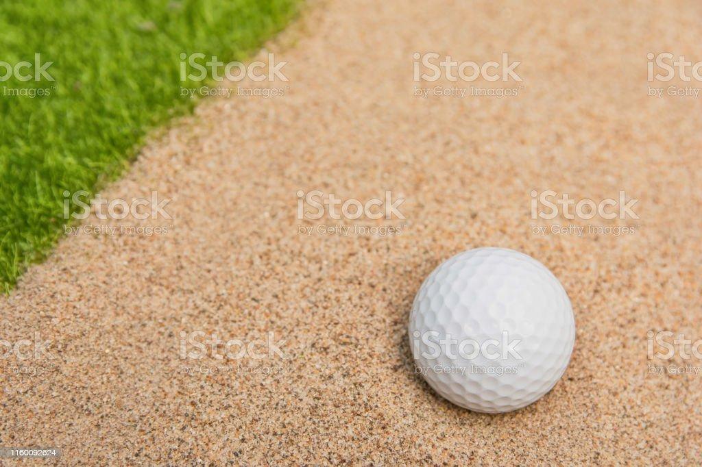 White golf ball in sand bunker on golf court
