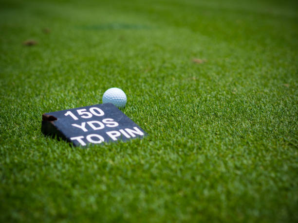 White golf ball on green grass fairway wood behind a yard label to pin on green in golf course stock photo