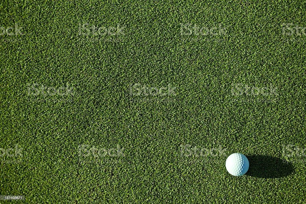A white golf ball on pristine green grass stock photo