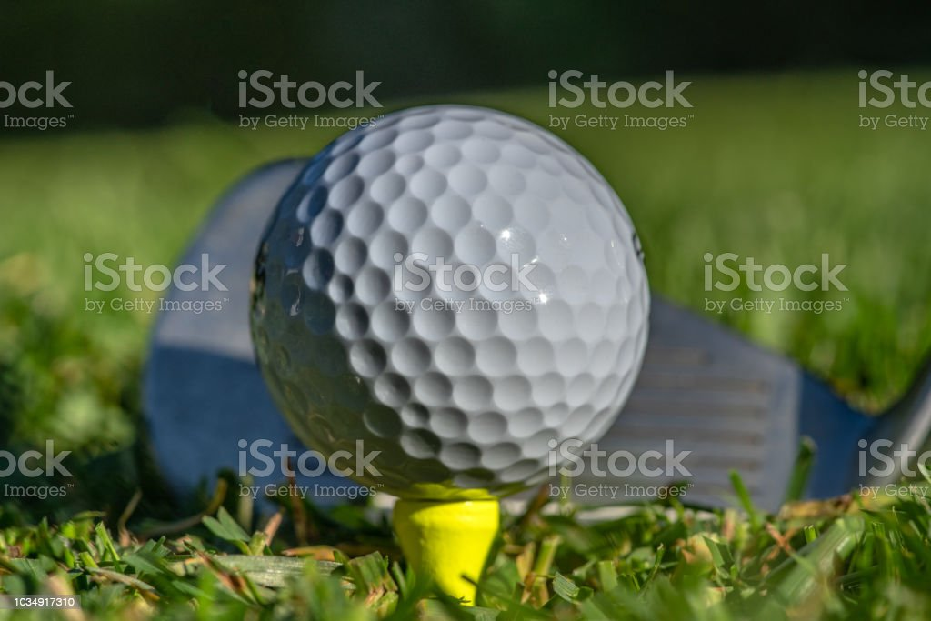 White golf ball teed up on a yellow tee in green grass and sunshine....