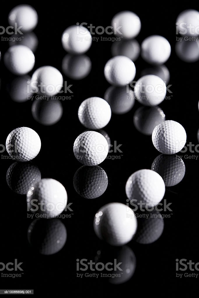 White golf balls on reflective black surface royalty-free stock photo