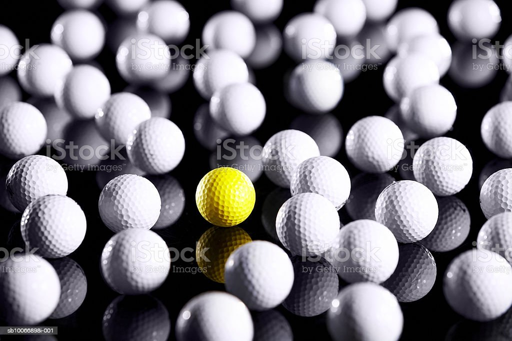 White golf balls with one yellow one royalty-free stock photo