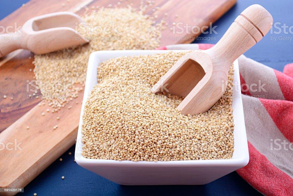 White grain quinoa on blue wood background. stock photo