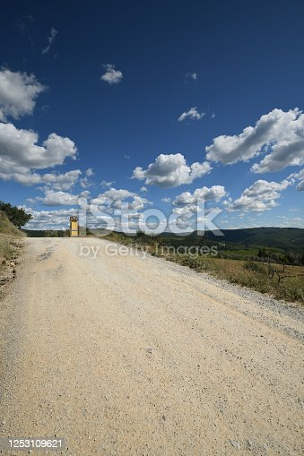 white gravel road and yellow broom flowers in the Tuscan countryside around Panzano in Chianti (Florence). Italy.
