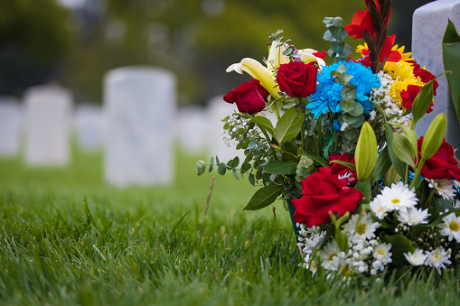 White gravestones and flowers at cemetary for memorial day