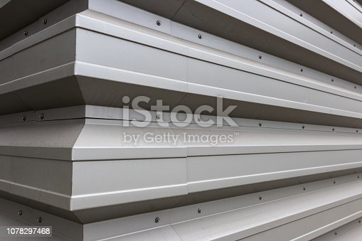 White gray aluminum siding corner with sheet metal screws
