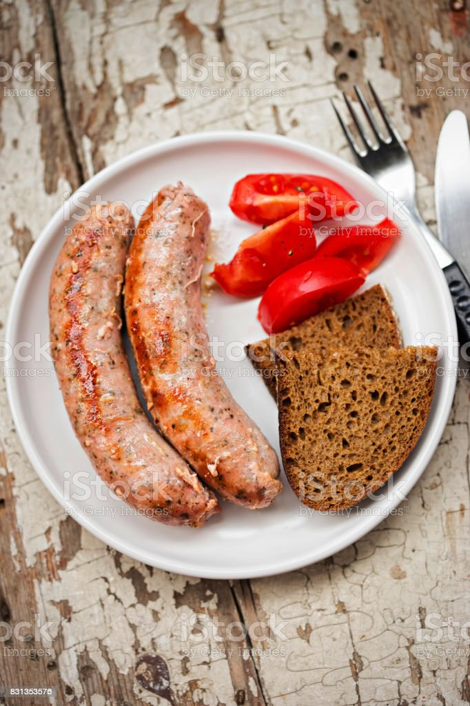 White grilled sausages with tomatoes and brown bread stock photo
