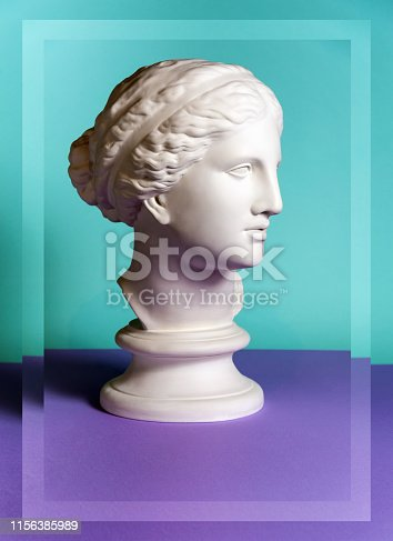 White gypsum copy of ancient statue of Venus de Milo head for artists on a green purple background. Plaster sculpture of woman face.