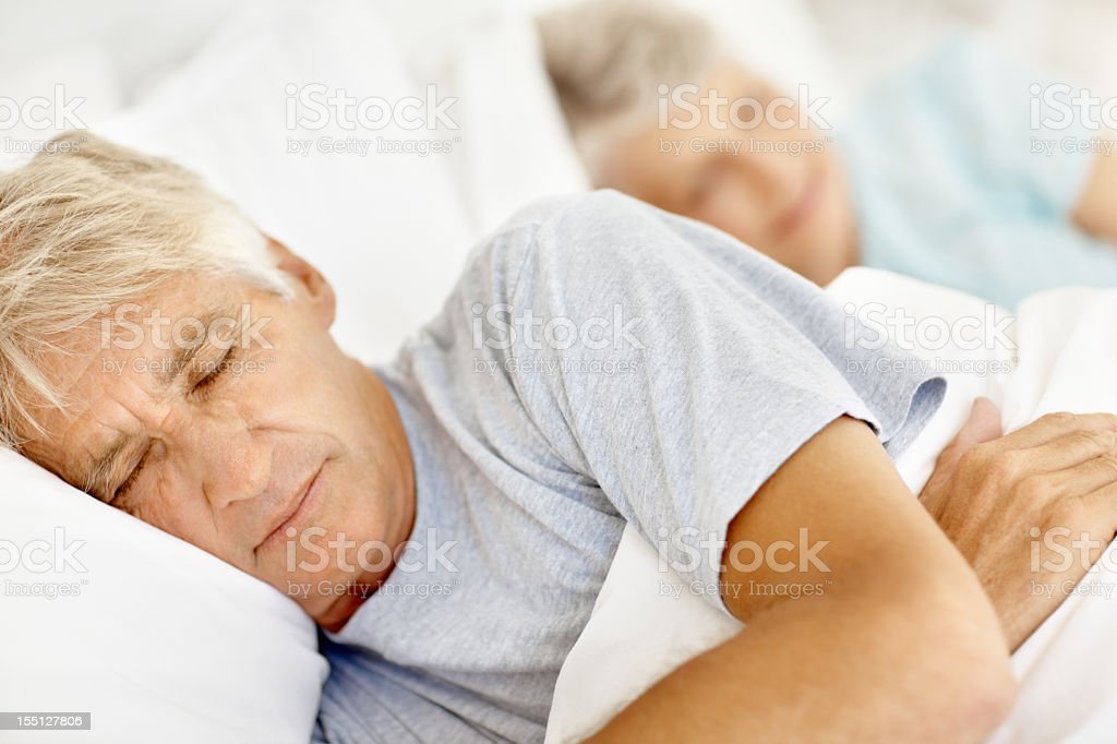 White haired man wearing grey top with eyes shut in bed royalty-free stock photo