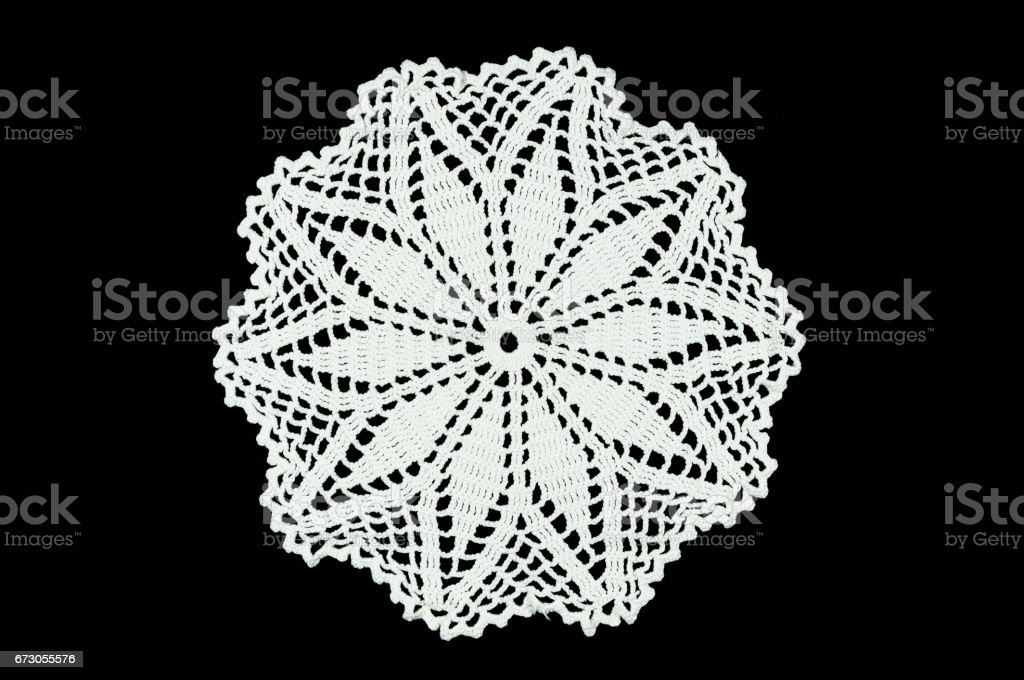 White hand made crocheted coaster on black background. Lace doily. stock photo